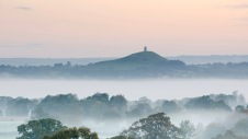 Mist shrouded fields leading towards Glastonbury Tor which dominates the flat landscape of the surrounding Somerset Levels.