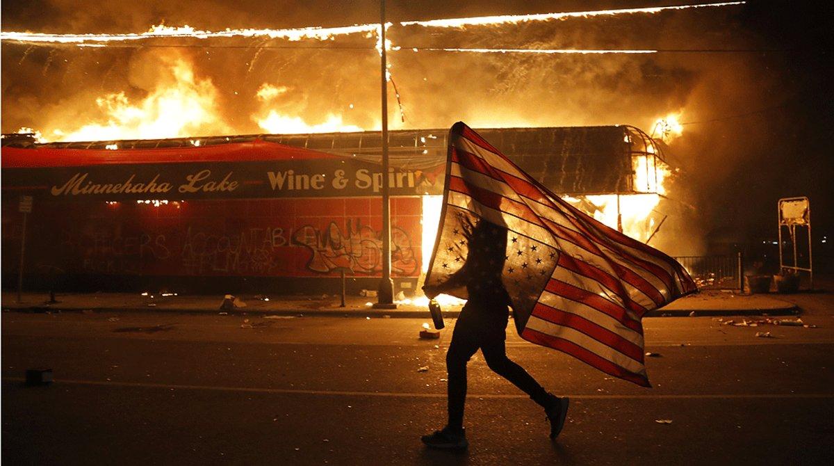 manifestante-porta-una-bandera-estadounidense-reves-junto-edificio-llamas-minneapolis-jueves-mayo-1590861344870-1.jpg